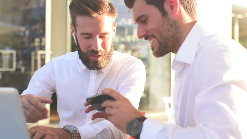 Portrait of two young handsome caucasian business man using smartphone talking to each other in city backlight and tapping the screen – business, work concept – side view