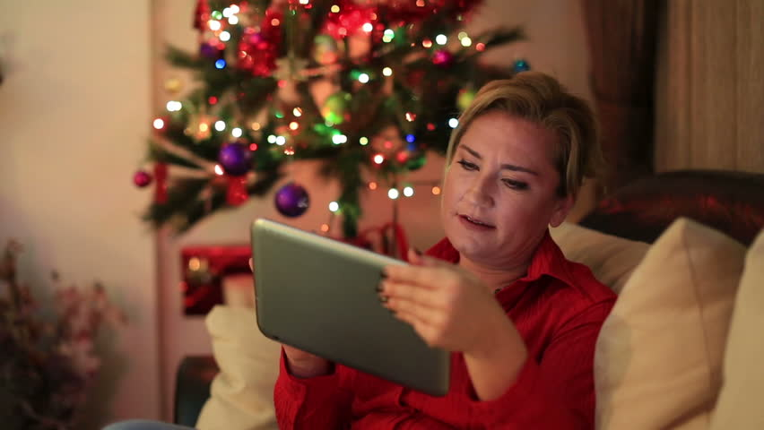 Portrait of a mid adult woman sitting on sofa near the christmas tree with digital tablet | Shutterstock HD Video #12949490