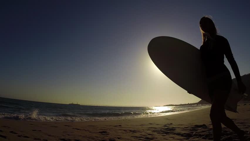 CIRCA 2015 - A surfer walks across the sunrise or sunset.   Shutterstock HD Video #12950690