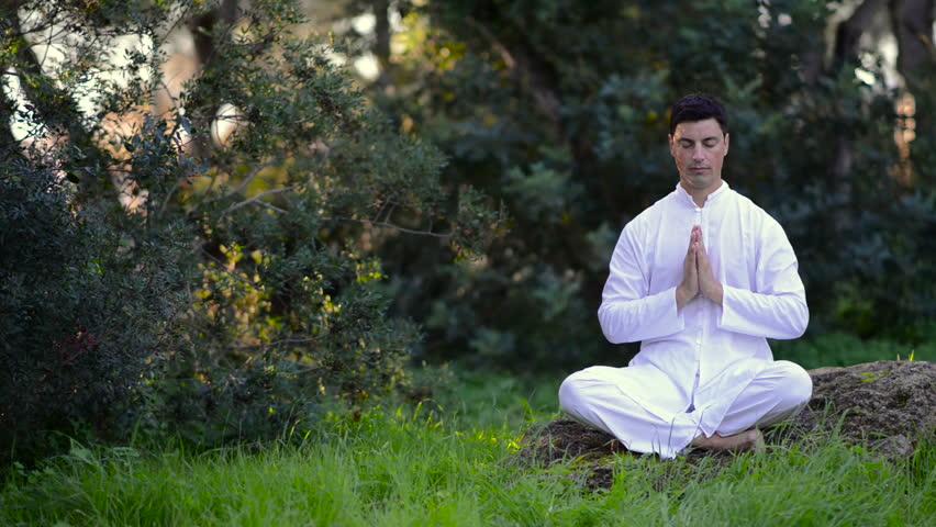 latin man meditating outdoors in a green park