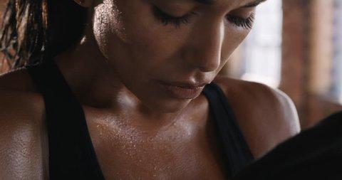 Beautiful Kickboxing gym woman training punching bag in fitness studio fierce strength fit body breathing slow motion