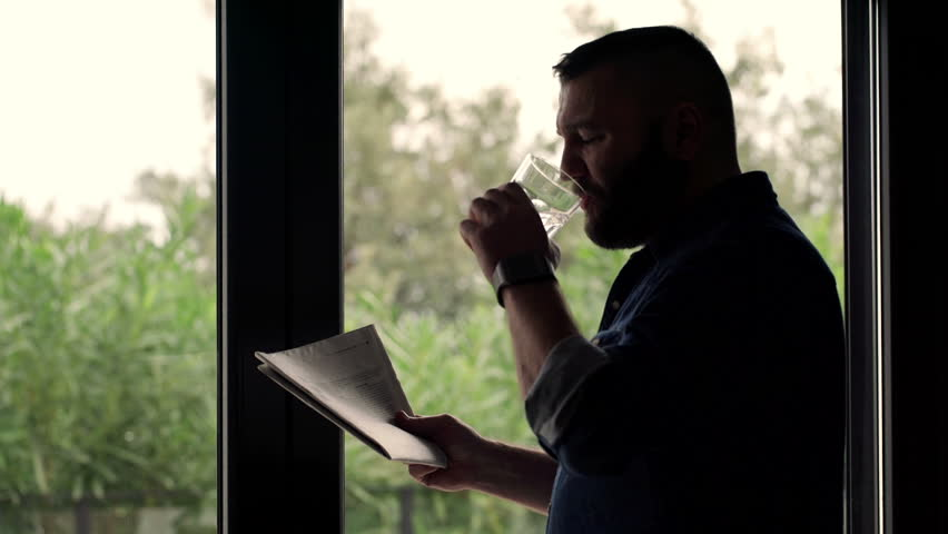 Young, handsome man drinking water and reading newspaper by the window  | Shutterstock HD Video #12968210