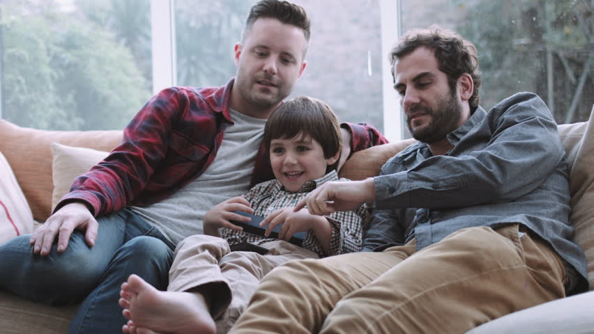 Same sex couple family watching TV on sofa