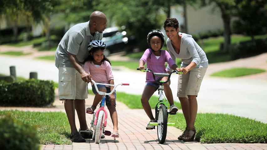 Little african american girls being helped to ride a bicycle by her parents