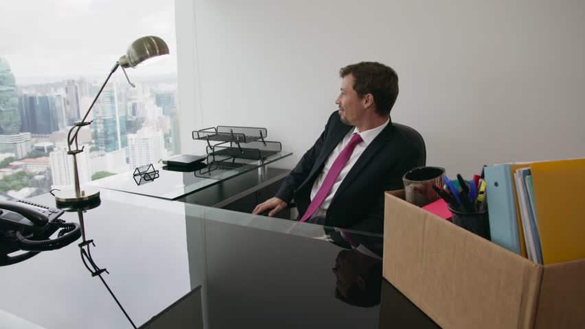 Businessman recently hired for corporate job moves into his new office. He holds a box with his folders and looks around with happy expression. Steadicam shot