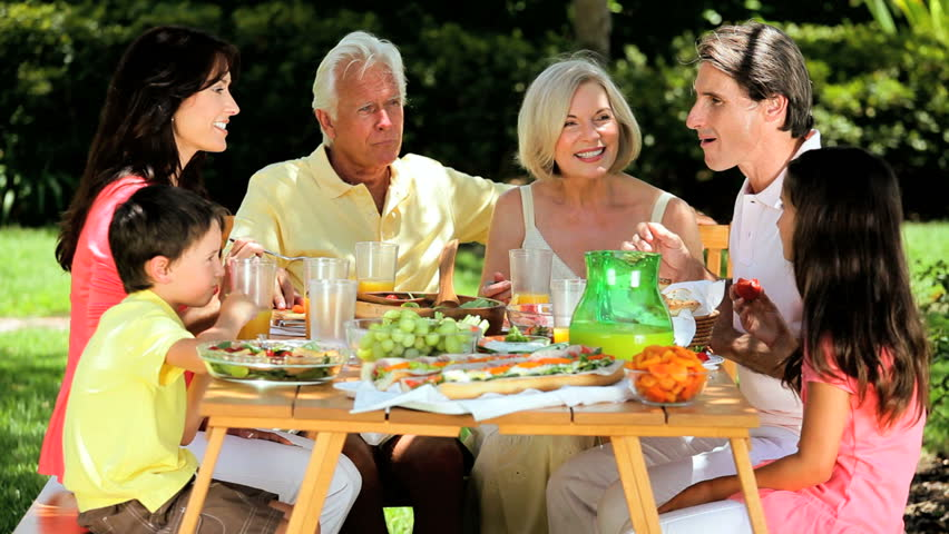 Three generations of a caucasian family sitting outdoors sharing a healthy lunch together | Shutterstock HD Video #1302310
