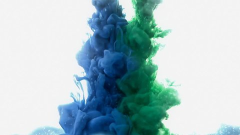 Green and blue ink dropping into water, creating clouds of colors.