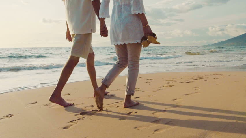Sunset Walk on a Luxury Beach. Older Couple Holds Hands and Walks Down the Beach at Sunset Getting Their Feet Wet