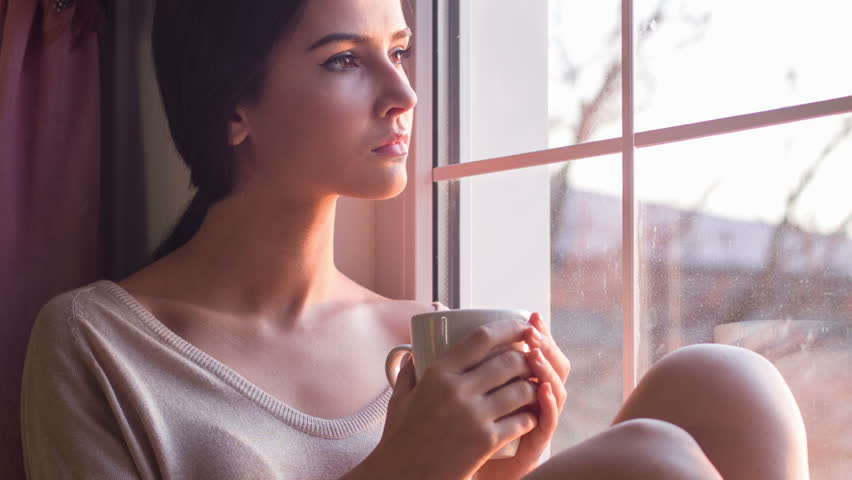 Melancholy time. Young miserable looking woman sits on windowsill and slowly drinks coffee.