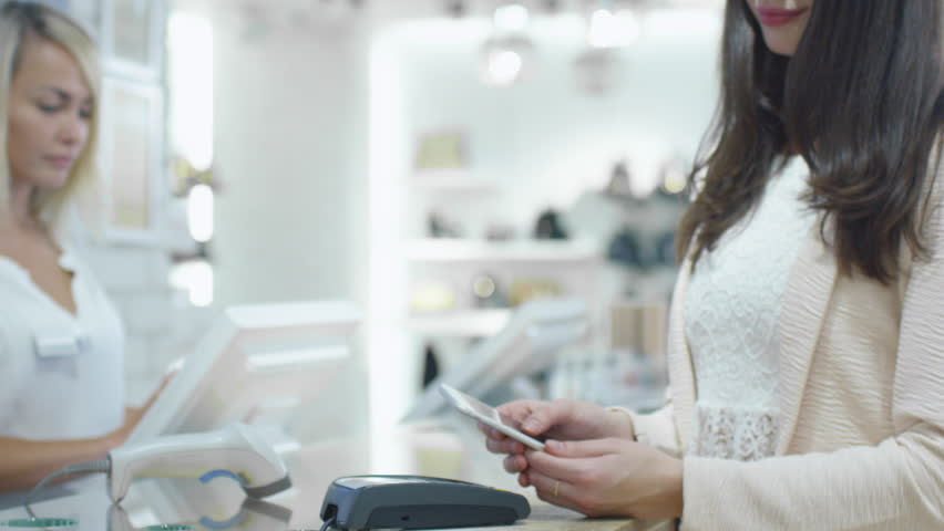 Young woman is paying with her smartphone application at the cash desk in a department store. Shot on RED Cinema Camera in 4K (UHD).   Shutterstock HD Video #13107986