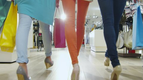Low shot of three girls that are walking through a clothing store in colorful garments. Shot on RED Cinema Camera in 4K (UHD).