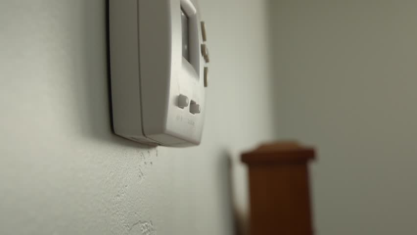 A dolly shot of a home thermostat on the wall in the bedroom | Shutterstock HD Video #13114685