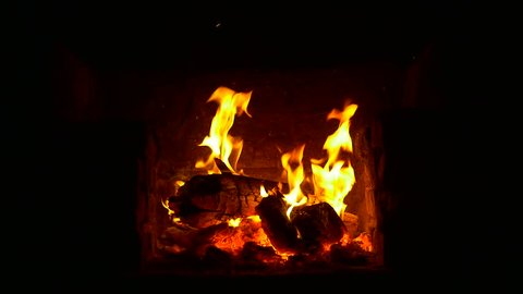 Crest of flame on burning wood in fireplace. 1 Minute, 30 fps footage of burning logs. A small pile of burning logs lit on the fire