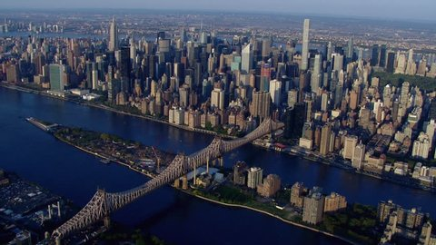 Aerial establishing shot of Midtown Manhattan over the East River, 59th Street Bridge and Roosevelt Island New York City on beautiful day. DX overhead point of view