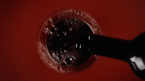 Pouring dark red wine in a glass. Shot from above. Eye-shaped shot.