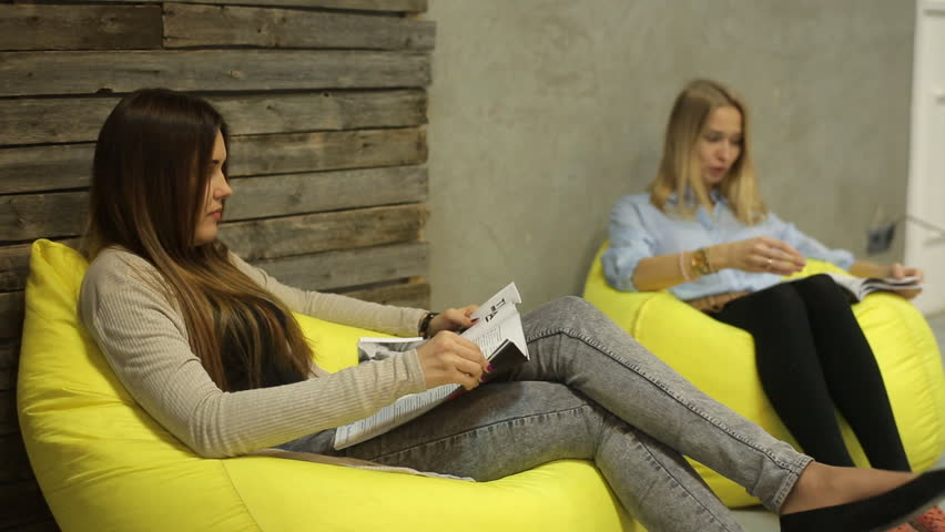 Two women relaxing and reading a magazine | Shutterstock HD Video #13130510