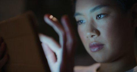 Beautiful asian woman using digital tablet computer technology at home late night shopping online reading social media blue glowing light on face