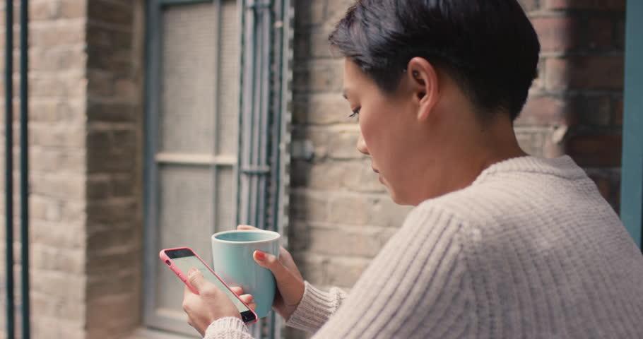 Beautiful asian woman using smart phone outside drinking coffee on a break | Shutterstock HD Video #13145150