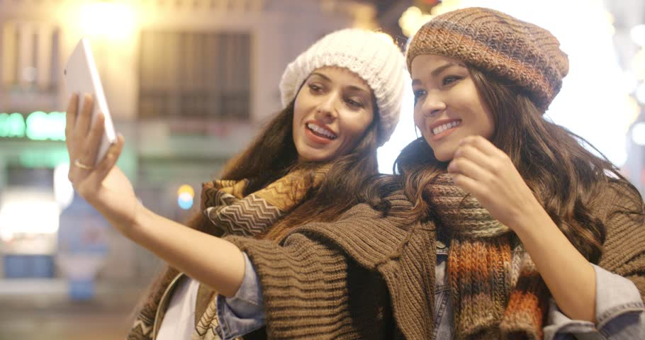 Two vivacious young women in trendy winter fashion standing close together outdoors in an urban street taking a selfie on a mobile phone | Shutterstock HD Video #13146035