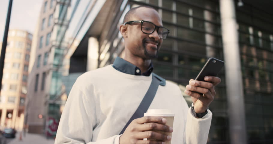 African American Man sms texting using app on smart phone in city. Handsome young businessman drinking coffee using smartphone smiling happy. Urban male professional commuting in his 20s | Shutterstock HD Video #13200089
