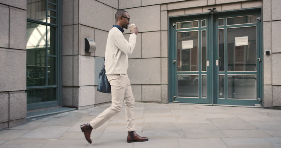 African american businessman walking in city drinking coffee commuting independently between glass buildings wearing glasses and smiling | Shutterstock HD Video #13200110