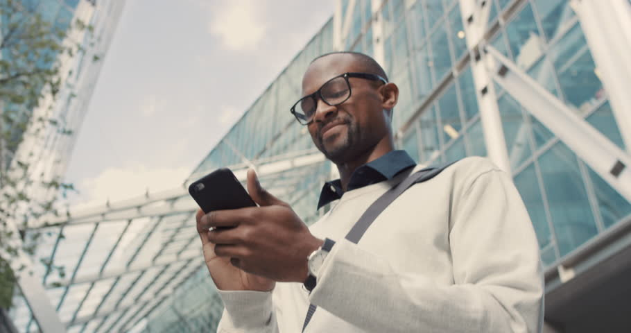 African American Man using business app on smart phone walking in city. Handsome young businessman communicating on smartphone smiling confident. Urban black male professional commuting in his 20s #13200200