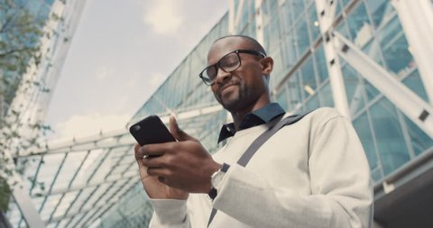 African American Man using business app on smart phone walking in city. Handsome young businessman communicating on smartphone smiling confident. Urban black male professional commuting in his 20s