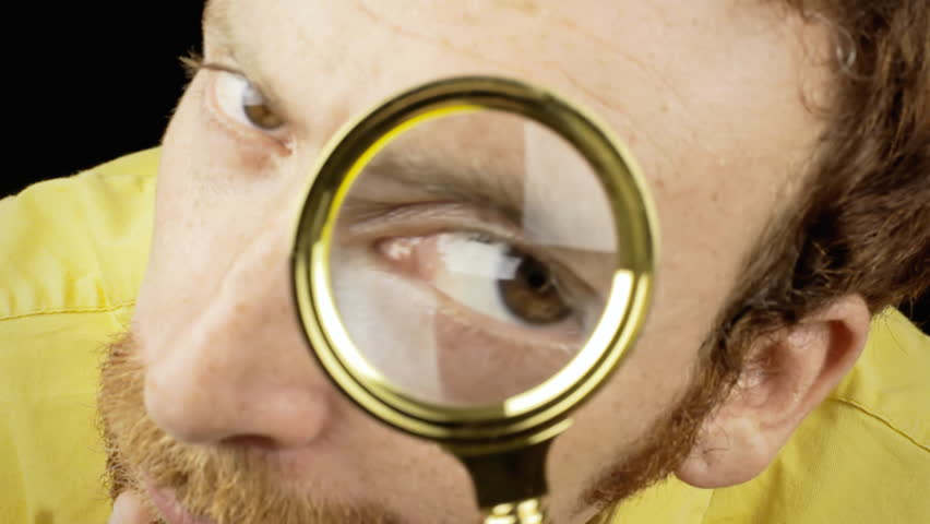 The big face of a curious man looking at the camera with a magnifying lens (a detective / private eye).