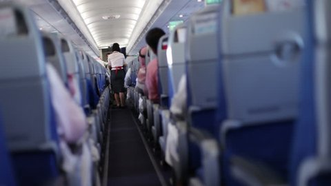 Dubai, CIRCA October 2015, UAE:  View of the passenger cabin of an airplane. Hostess walking on the corridor during flight.