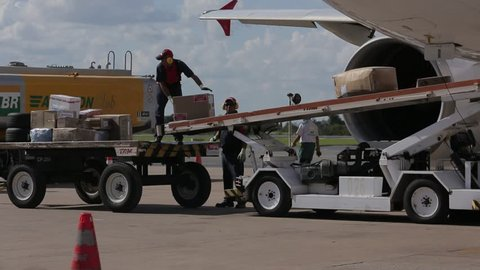 AIRPORT RUNWAY - Workers offload boxes from the cargo hold of a commercial airplane. - Santiago, Chile, July, 2014