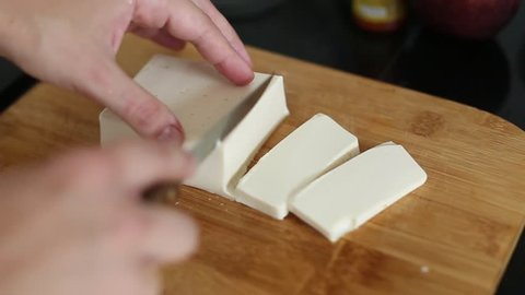 Cutting tofu with knife on a cutting board