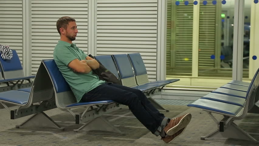Unhappy male passenger sitting at waiting room, flight canceled or delayed. Young man wasting time in terminal, disappointment, bad airport service. Expecting person feeling bored at railway station