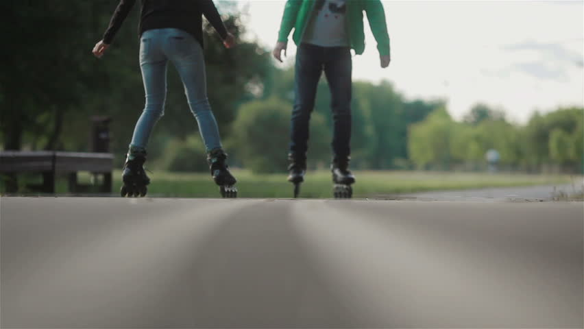 Male and female rollerblading and doing tricks with skates in park on a summer day #13264280