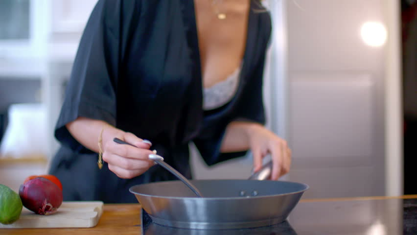 Sexy busty woman cooking in the kitchen bending forwards as she stirs the food in the frying pan  close up view of her hands and midriff