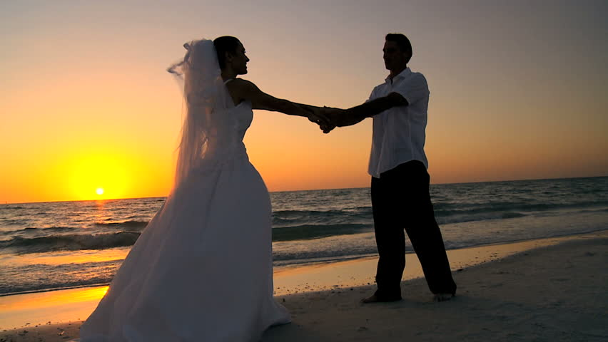 Bride & groom in silhouette dancing at sunset on the beach after their wedding filmed at 60FPS