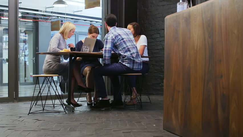 Young diverse team in online startup company having brainstorm meeting discussion collaboration in trendy cafe coffee shop with free wifi | Shutterstock HD Video #13300574