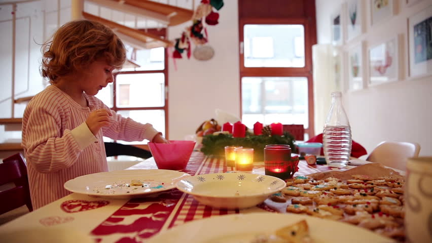 A little girl nibbles on sugar decoration while icing cookies and treats on advent first