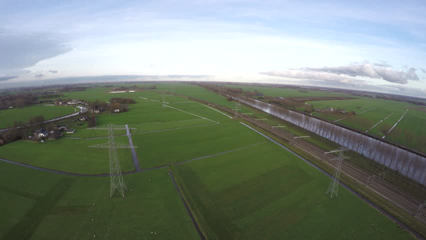 Aerial flying above and between transmission towers electricity pylons used for distribution of power through steel overhead cables running in between iron towers green grass landscape and canal 4k