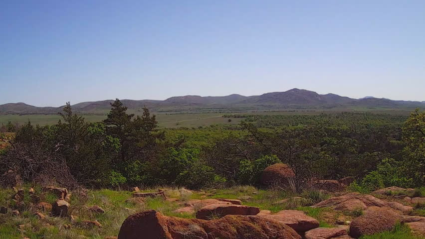 LAWTON, OK/USA: May 1, 2015- The camera pans a wide vista shot of a forested valley and distant mountain in the Wichita Mountains Nature Reserve In South Central Oklahoma.