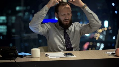 Angry businessman throwing laptop in office at night