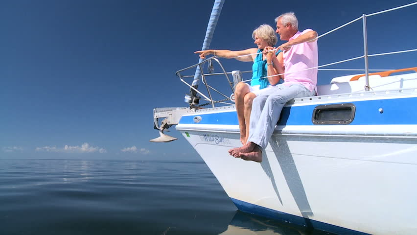 Healthy retired couple enjoying leisure aboard their luxury sailing boat filmed at 60FPS | Shutterstock HD Video #1332673