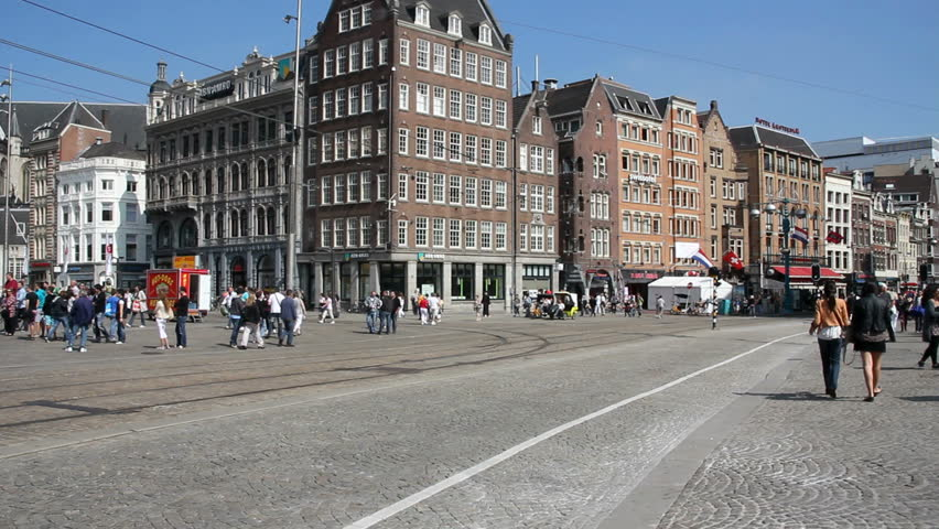 AMSTERDAM, HOLLAND - AUGUST 1: Tram drives along Dam square, with tourists crossing the street, on August 1, 2011 in Amsterdam, Holland.