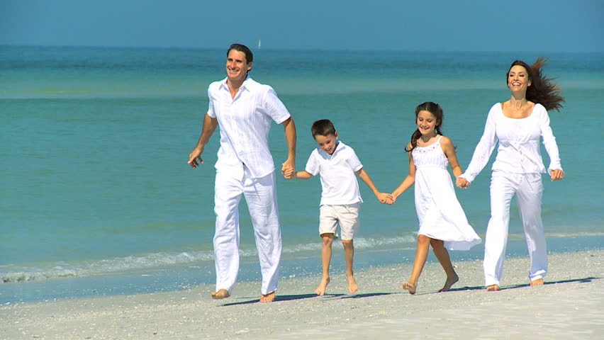 Happy young family having fun on vacation skipping outdoors on the beach filmed at 60FPS | Shutterstock HD Video #1333828