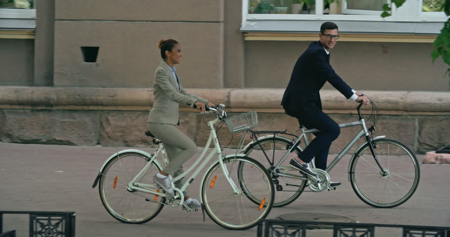Tracking shot of elegant business couple biking down the street and talking  | Shutterstock HD Video #13350650
