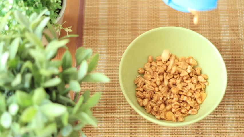 Pouring cornflakes into a bowl, slow motion, top view