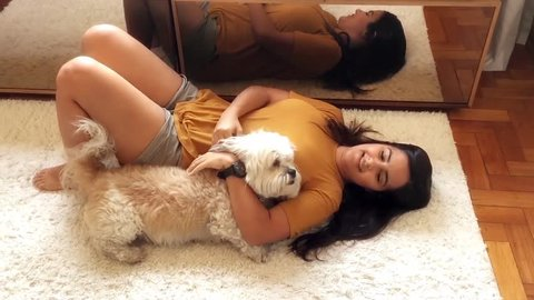 Young brazilian woman playing with her dogs in the living room.