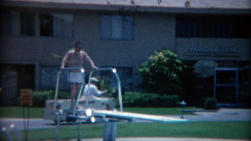 LAS VEGAS 1965: Fat man jumping off hotel pool diving board making big splash.