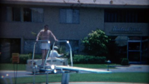 LAS VEGAS 1965: Fat man jumping off hotel pool diving board making big splash.