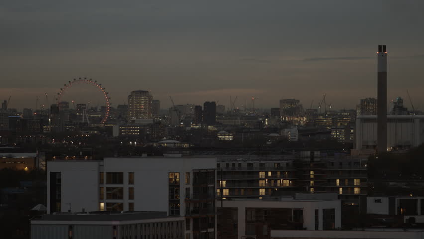 London skyline at dusk with expensive apartments in the foreground. London Eye and the Wembley Stadium can be seen in the distance.