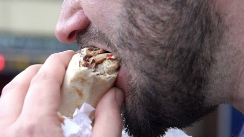 close up footage of a male mouth eating a sandwich